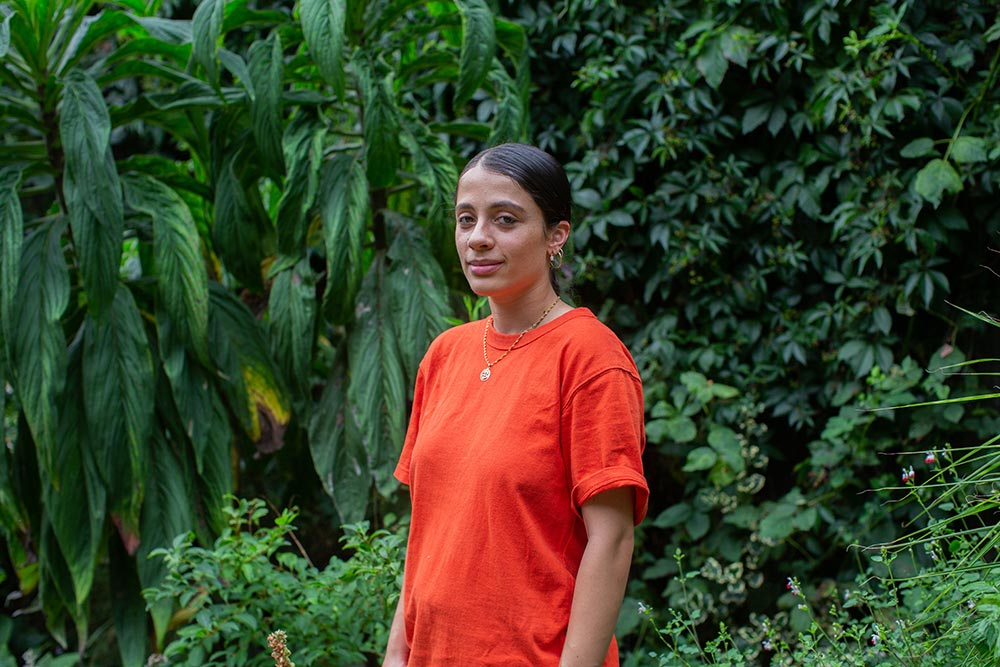 Artist Meera Shakti Osbourne standing in front of trees wearing an orange t-shirt