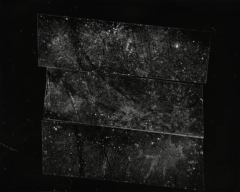 A print of a black and white photogram. The image is deliberately designed to be ambiguous, white dots and lines are imprinted on three rough lines that are placed closely together in the loose shape of a square. The more you stare at the image the more patterns and images you see in it. You can see the vague outlines of what looks like the magnified palm of a person's hand.
